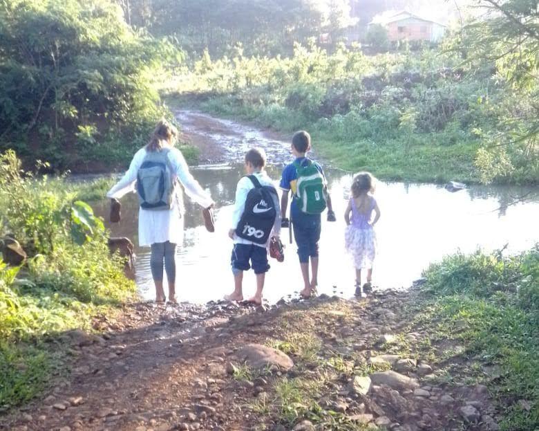 Niños cruzan por un arroyo para llegar a la escuela por falta de puente