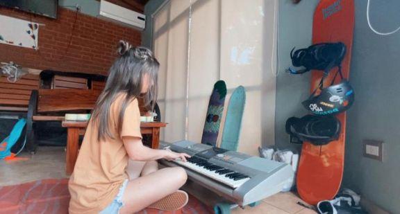 Antonella Olivera practicando con su teclado en el quincho familiar